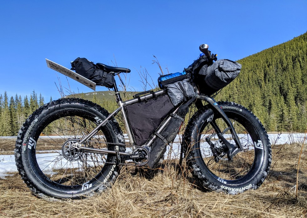 Fatbike on a recent overnighter, loaded with gear, food, and water for -20 Celsius. The luggage consists of: SeatBag with DIY fender, DIY high volume custom frame bag, BikeHandle, FenderBag, BottleCradle and XL StraddleBag on each side of top tube, HandlebarRoll - variable volume (new product coming soon), Jones H-Loop Harness, and a pair of StraddleBags mounted to the back of the handlebars. The total weight of all luggage is about 1,250 grams (2.8#). Each piece of luggage has more than 1,000 km of usage. The FenderBag is at about 3,000 kilometres. Not visible are the Tool & Repair Rolls hidden in each end of the handlebars. While bulky, the weight on the handlebars is less than 2,500 grams (5.6#)