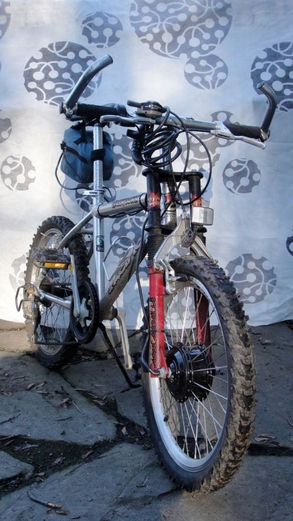 """JJ has a small bmx bike with 20"""" wheels and ornamental shock absorbers. I installed a $500 geared front hub motor from Ebike-kit.com."""