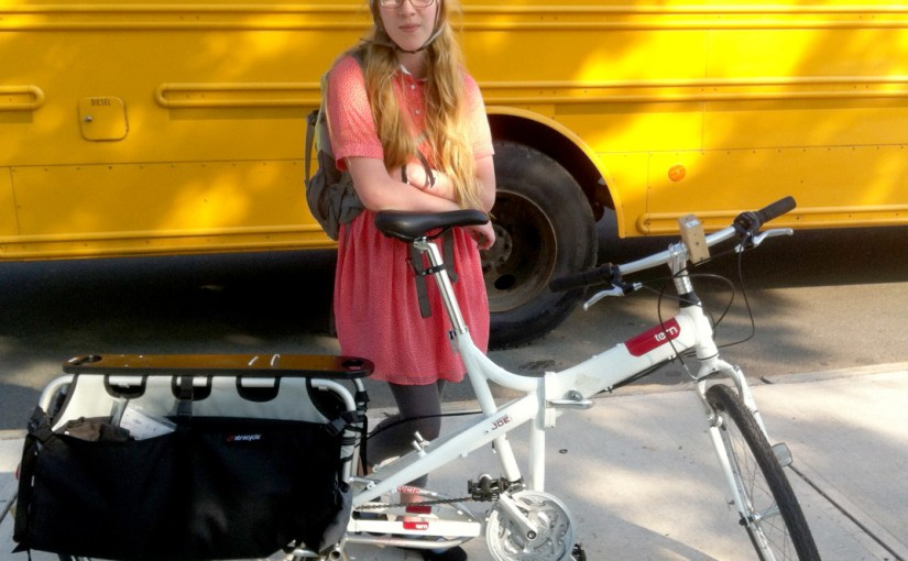 girl in front of school bus with folding cargo bike
