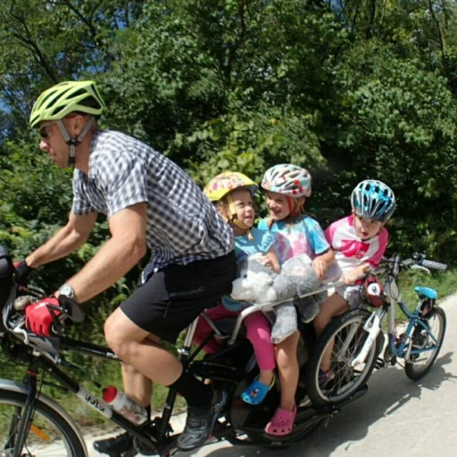"Don Galligher carrying three girls and a 20"" bike up a hill"