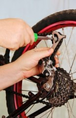 hand of the master with a wrench, repair a bicycle wheel.