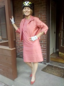Barb Chamberlain in apricot silk dress and jacket with matching leather pumps, wearing a bike helmet.