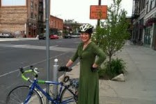 Barb in green jersey dress with helmet and gloves and her road bike set up for commuting.
