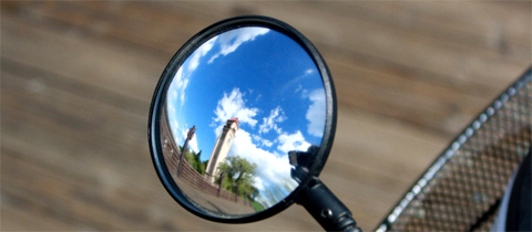 Blue sky with clouds and Riverfront Park clock tower reflected in a bike mirror. Photo by Andrea Parrish.