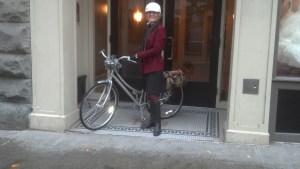 White woman in black skirt, black boots, crimson long jacket, holding silver upright bike, wearing white helmet.