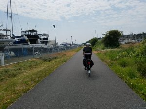 Man on bike trail riding past several boats in a boatyard.
