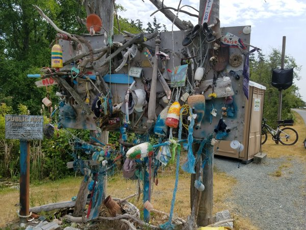 Public art installation on the Tommy Thompson Trail in Anacortes, WA. Large posts with netting, many items dangling from the netting including buoys, fabric, other mementos people have attached. Sign invites people to add things.