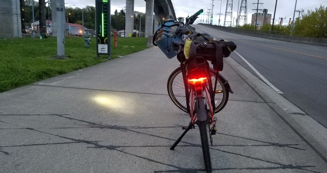 Looking west on the West Seattle Bridge sidewalk at dusk. Bike counter at left. Bike facing up the hill away from photographer with headlight shining on the sidewalk, taillight on, medium blue handlebar bag, black bag strapped to back rack.