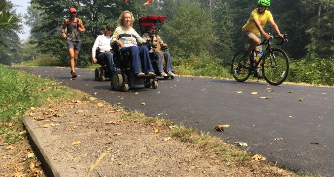 Ian Mackay (in power wheelchair with red awning) finishing his trip east to west across Washington state in 2018 with friends riding, rolling and running on the Olympic Discovery Trail.