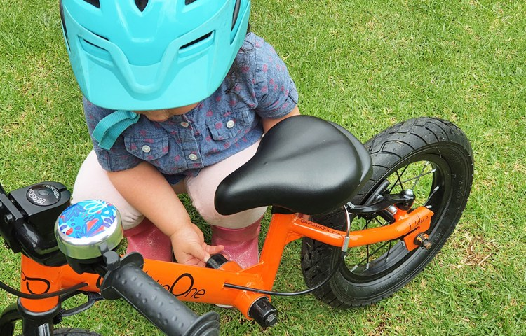 Niña ajustando bicicleta de aprendizaje