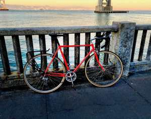 Red bicycle against the waterfront on the embarcadero under the Bay Bridge in San Francisco