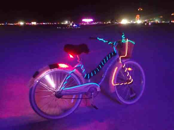 Burning Man at night with a bike covered in lights.