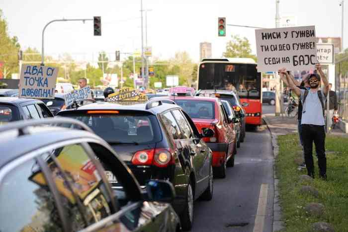 A traffic jam with bike advocates holding up signs.