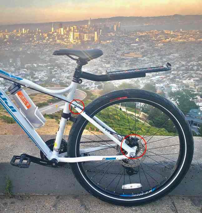 A mountain bike up on the san francisco twin peaks overlook, but more importantly it has disc brakes and the connection points are circled to show that it needs a disc brake specific rack. It also has a seatpost rear bike rack attached instead.
