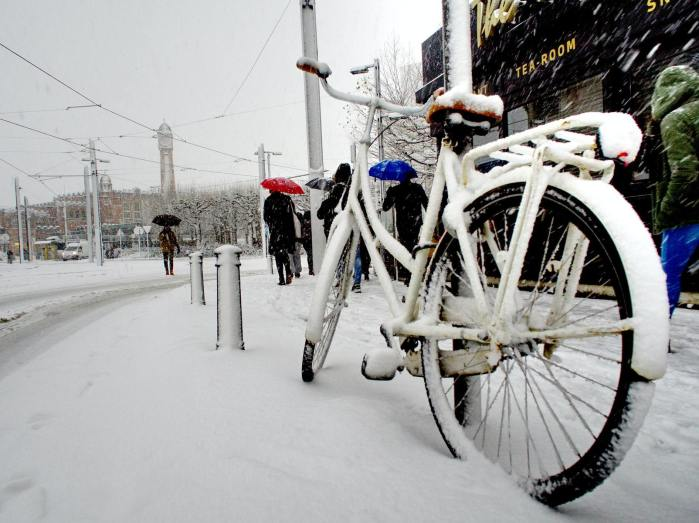 A step through bicycle parked with a u-lock and covered with snow along a snowy street.