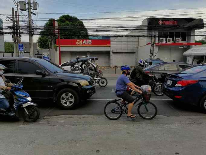 a lone cyclist weaving through car traffic in pasig city, manila