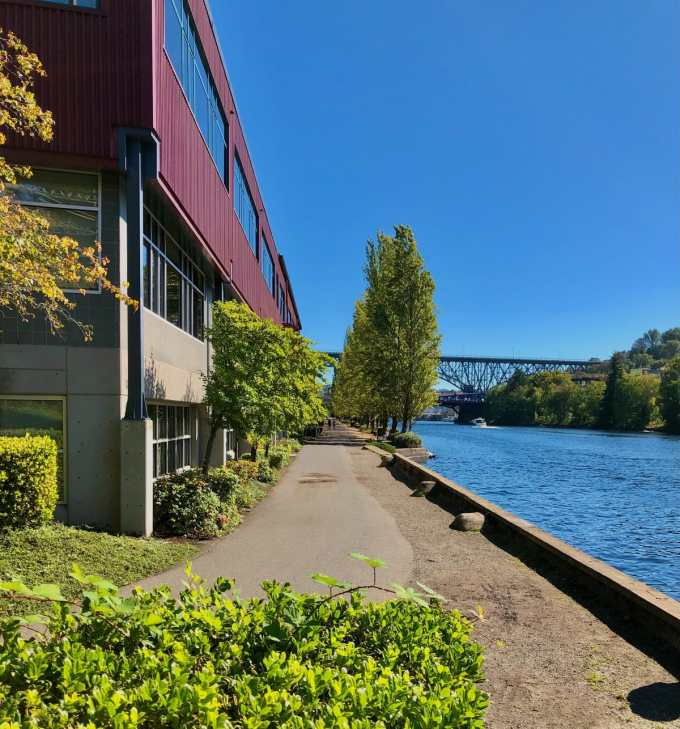 A beautiful section of burke gilman trail next to the shipping canal with a bridge in the background
