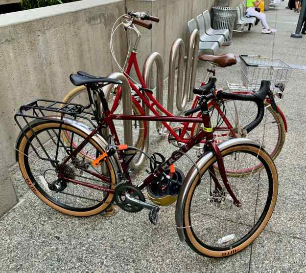 two commuter bikes secured to a bike rack. no one is stealing anything.