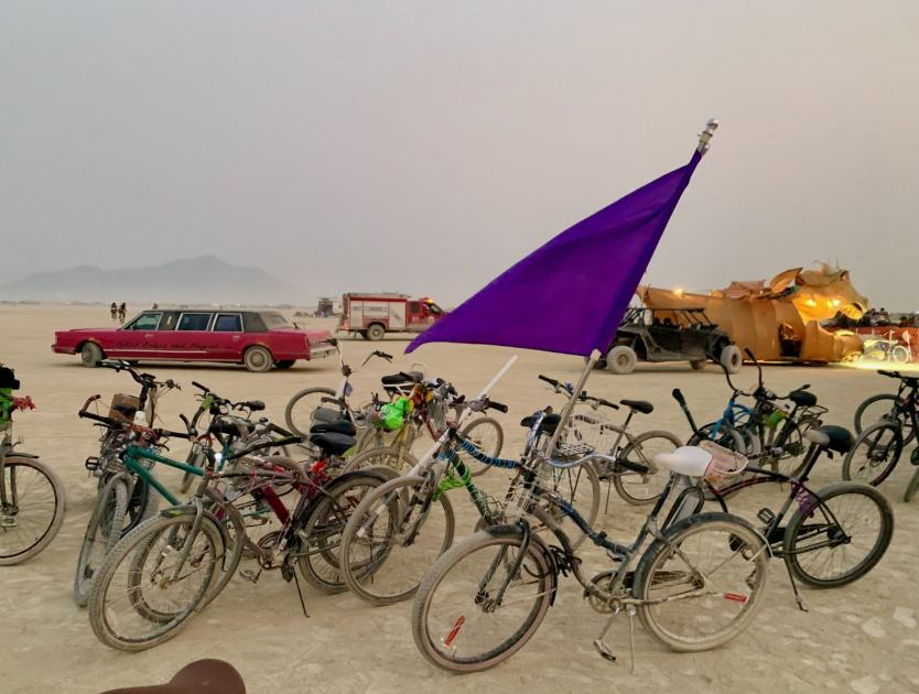 a bunch of bicycles with a purple flag with some art cars in the background