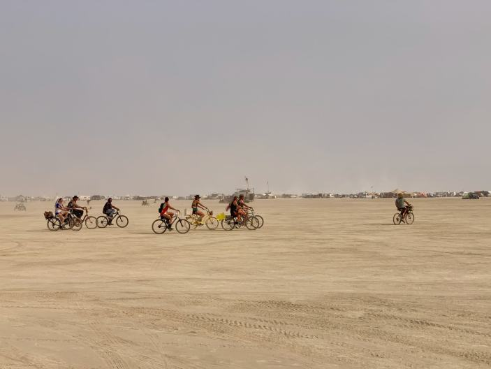 group of people on bicycles riding through the black rock city desert at burning man