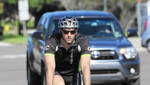 Brett Schaefer, owner of South Lake Bike and Tri in Minneola, shares the road with heavy traffic while crossing U.S. Highway 27 at Washington Street. (Tom Benitez, Orlando Sentinel)