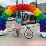 Drag queen Luna Flare with a RideKCBike under a rainbow arch