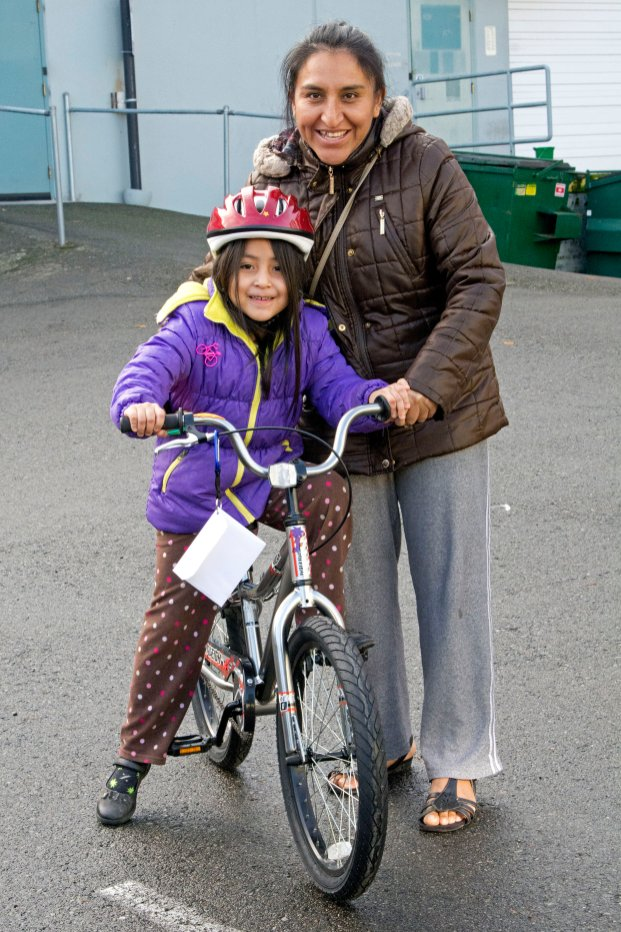 A happy family ready to head home with their new bicycle.