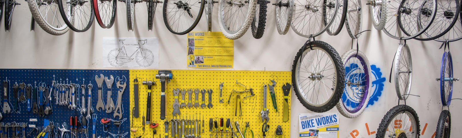 Several bicycle tires arrayed across the top with a blue and yellow pegboard full of tools