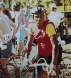 A man in a red jersey on a bicycle in a crowd of cyclists getting ready for a race.