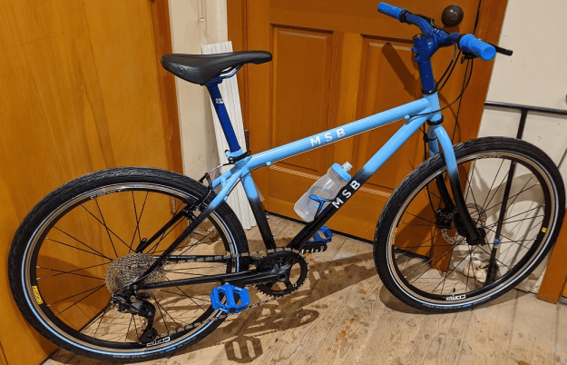 A bike with dark blue handlebars and grips, a light blue and black frame, and blue pedals.
