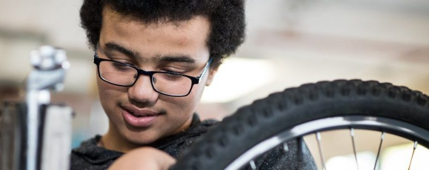 A youth with glasses works on a bike