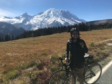 A person on a bicycle poses in front of a snow-capped mountain