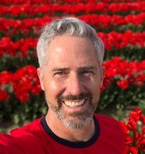 A close up of a man's bearded face in front of a field of red flowers.