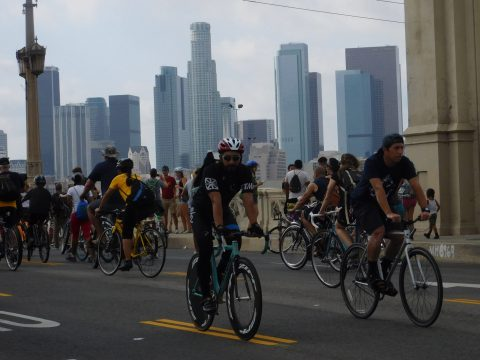 Downtown forms a backdrop for riders on the 4th Street bridge