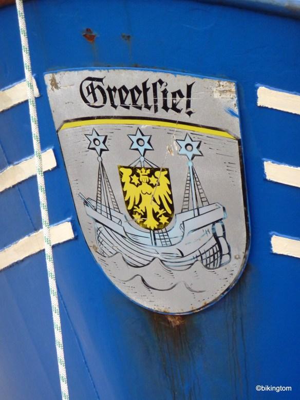 Das Wappen der ehemaligen Gemeinde Greetsiel auf einem Schiffsbug