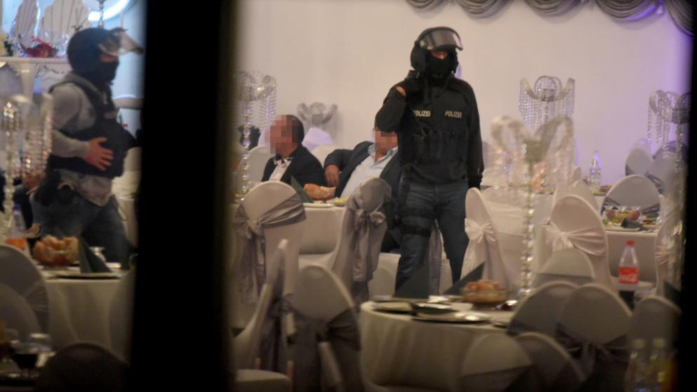 Eine verstörende Szene: Der Polizist der Spezialeinheit steht vermummt und bewaffnet inmitten der romantischen Hochzeitsdeko