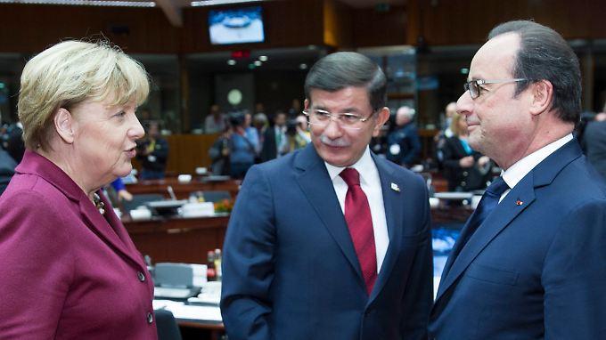 Kanzlerin Angela Merkel, der türkische Premier Ahmet Davutoglu und Frankreichs Präsident Francois Hollande unterhalten sich auf dem Gipfel in Brüssel.