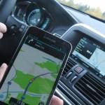 Volvo XC60 2015 med Sensus navigation på centralskärmen. I förgrunden en Samsung Note mobiltelefon med navigeringsappen Waze visande samma rutt på kartan.