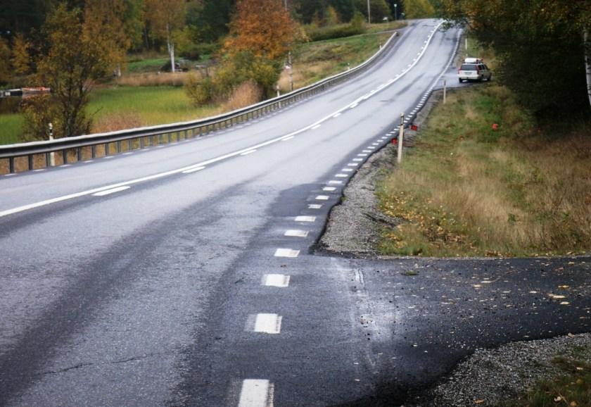Foto på olyckskurvans utgång med markeringar av spår och delar från olycksbilen.