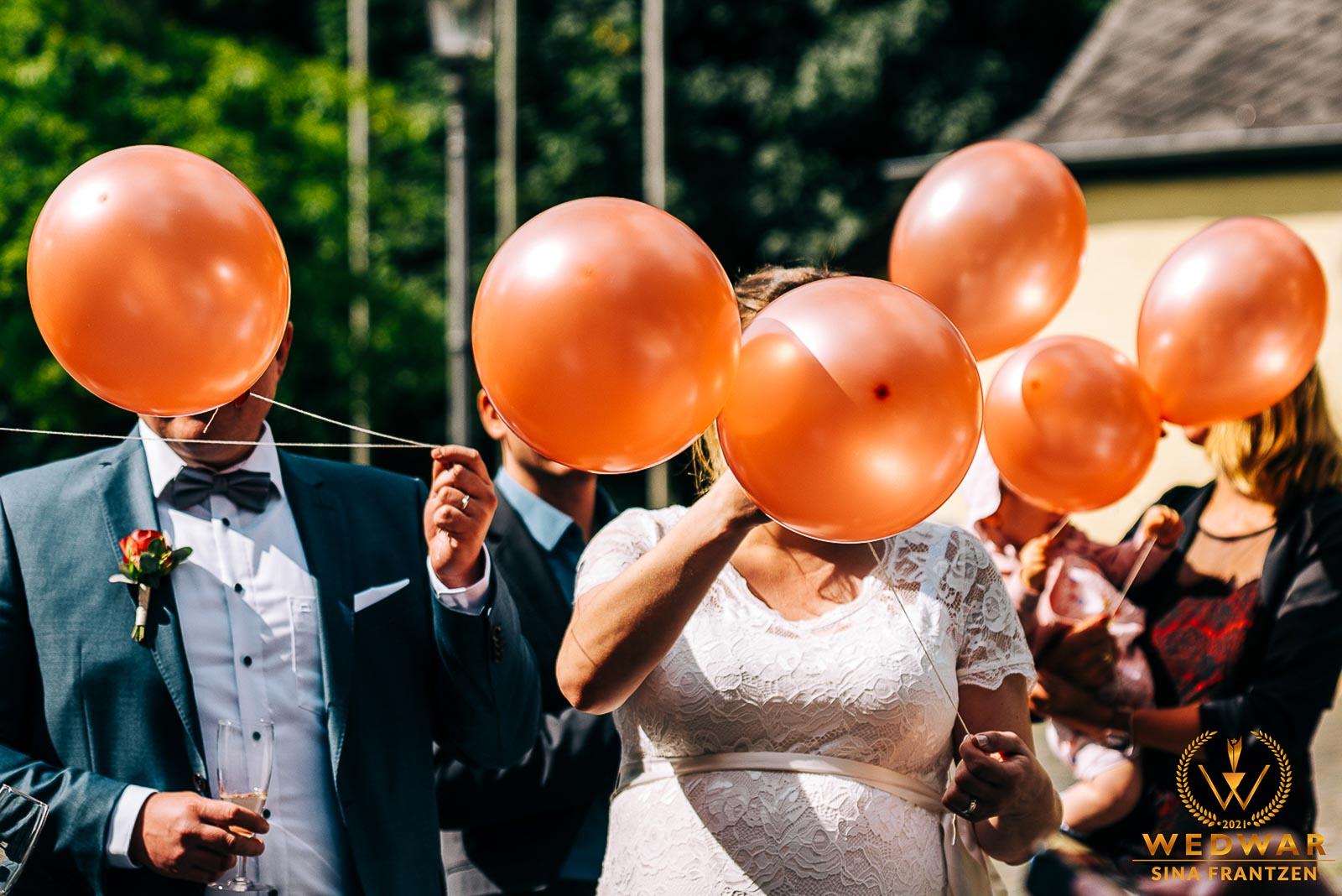 Ballons vor den Gesichtern einer Hochzeitsgesellschaft - Gewinnerbild Wedwar WAC-18