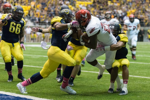 NAU's Eddie Horn grabs a handful of facemask to prevent Eastern Washington's Quincy Forte from reaching the end zone