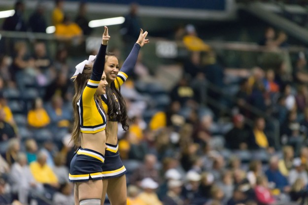 Cheerleaders celebrate a Northern Arizona touchdown during a college football game at the J. L. Walkup Skydome in Flagstaff, Arizona. This photo was made with a Nikon D610 and 200-500mm f/5.6E at 500mm, f/5.6, ISO 8063, 1/500-second. It has been cropped and processed to taste in Adobe Lightroom. (Bill Ferris)