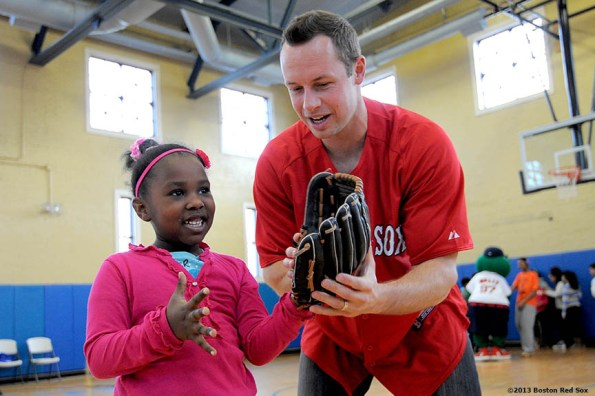 """""""Boston Red Sox outfielder Daniel Nava gives fielding advice to Treasure Blackwell, 6, at the Vine Street Community Center in Roxbury, MA. Nava, along with Red Sox pitcher Andrew Bailey and Wally the Green Monster, visited the center to run baseball clinics, answer questions, and pose for photographs."""""""