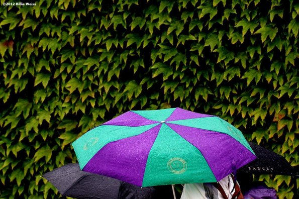 """""""Fans walk under umbrellas during a rain delay at the Championships Wimbledon Monday, July 2, 2012 at the All England Lawn & Tennis Club in London, England."""""""