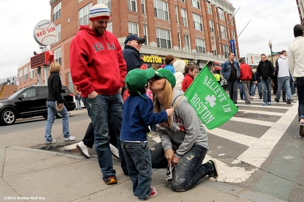 """""""Shawna Salomon of Auburn, Massachusetts kisses her son, Jacob, 3, as Blake Ratcliffe of Brighton, Massachusetts watches on Yawkey Way during the first Boston Red Sox home game after the attacks on the 2013 Boston Marathon Saturday, April 20, 2013."""""""