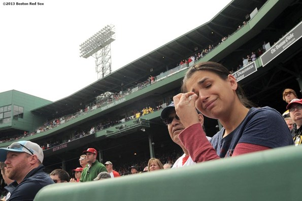 """""""A fan wipes tears away during a pre-game ceremony honoring the victims, first responders, and others involved in the attacks on the 2013 Boston Marathon Saturday, April 20, 2013."""""""