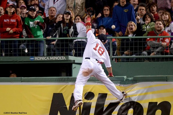 """""""Boston Red Sox right fielder Shane Victorino climbs the right field wall as he attempts to catch a home run by Minnesota right fielder Oswaldo Arcia during the fourth inning of a game against the Minnesota Twins Thursday, May 9, 2013 at Fenway Park."""""""