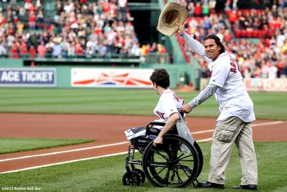 """""""Jeff Bauman, who lost both of his legs during the Boston Marathon bombings, is wheeled onto the field by Carlos Arredondo, a Marathon spectator who carried Bauman to safety, before throwing out the ceremonial first pitch before a game between the Boston Red Sox and the Philadelphia Phillies at Fenway Park in Boston, Massachusetts Tuesday, May 28, 2013."""""""