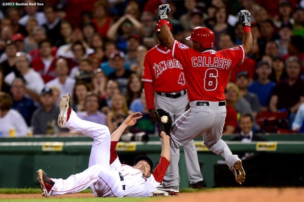 """""""Boston Red Sox pitcher Clay Buchholz dives as he tags out third baseman Alberto Callaspo during the fourth inning of a game against the Los Angeles Angels of Anaheim Saturday, June 8, 2013 at Fenway Park in Boston, Massachusetts."""""""