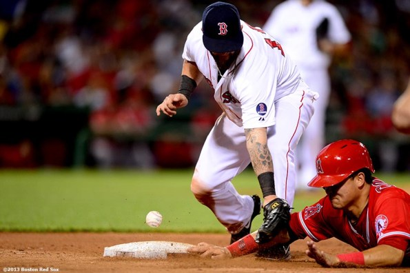 """""""Boston Red Sox first baseman loses the ball as he applies a tag to catcher Hank Conger on a pickoff during the seventh inning of a game against the Los Angeles Angels of Anaheim Saturday, June 8, 2013 at Fenway Park in Boston, Massachusetts."""""""